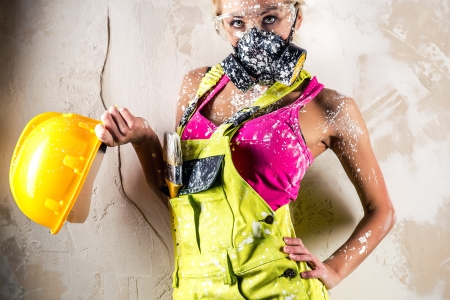 coverall: Female construction worker wearing respirator posing over obsolete wall