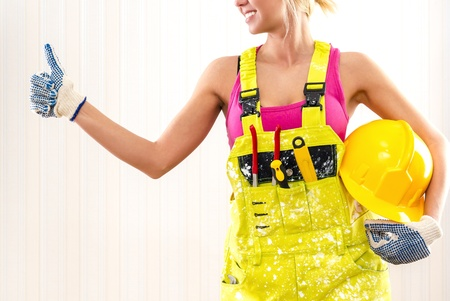 studio happy overall: Woman in coverall holding hard hat and showing thumbs up