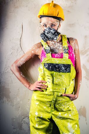 respirator: Female construction worker wearing respirator posing over obsolete wall