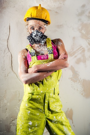 dust mask: Female construction worker wearing respirator posing over obsolete wall