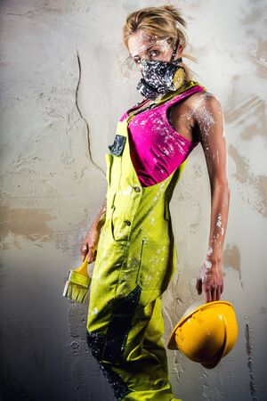Female construction worker holding paint brush and hard hat over obsolete white background photo