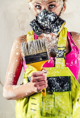 Female construction worker wearing respirator holding paint brush  photo