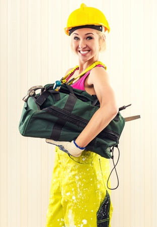 studio happy overall: Smiling female construction worker with tool bag posing indoors