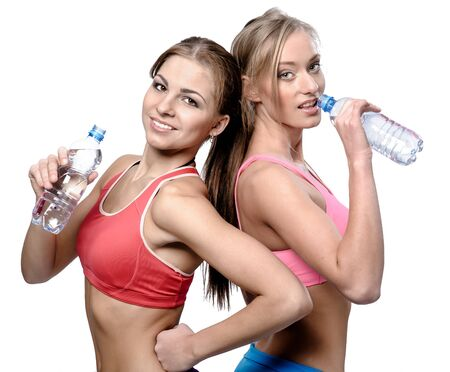 Two beautiful young women drinking water after fitness exercise photo
