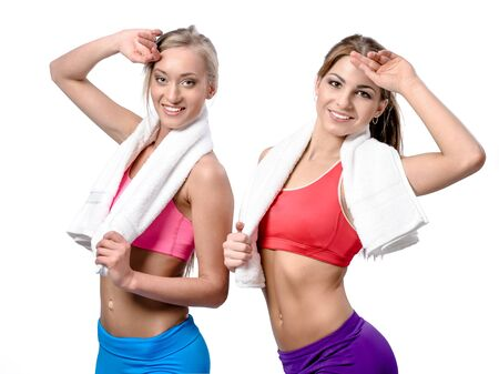 Two beautiful girls after workout with towels on white background photo