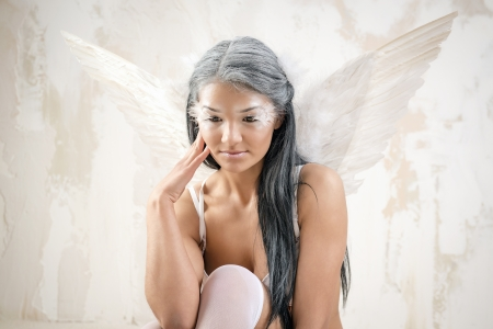 Young woman as angel with white wings over white obsolete wall  photo