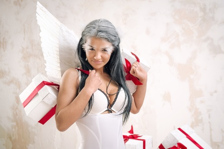 Young woman as angel with heap of gift boxes posing indoors photo