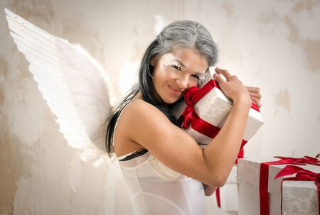 Young woman as angel with heap of gift boxes  photo