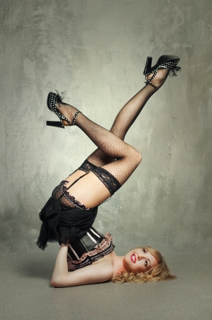 Sexy blond pin up girl over grey background photo