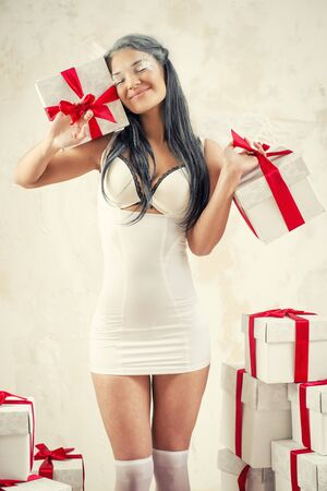 Beautiful young woman as angel with heap of gift boxes posing indoors photo