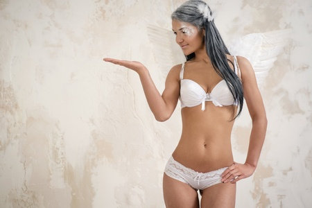 Young woman as angel showing something with the hand over white obsolete background photo
