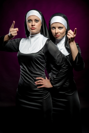 Attractive young nuns posing indoors photo