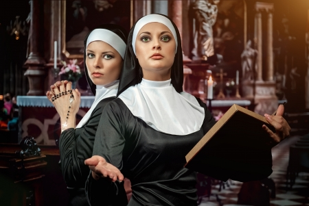 Two attractive young nuns with rosary and bible praying in the church photo