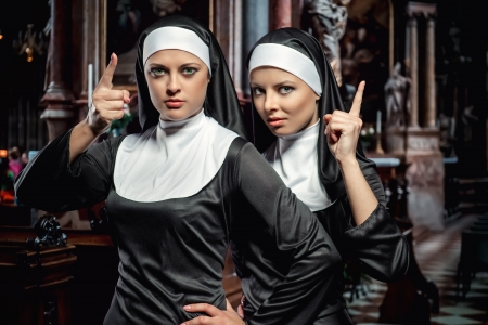 Attractive young nuns posing in the church photo