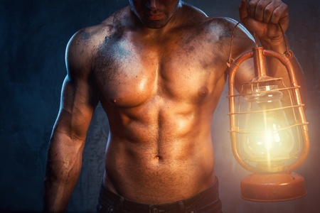 Muscular man holding oil lamp Stock Photo - 20834464