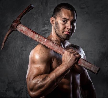 Muscular man holding pickaxe Stock Photo - 20834470