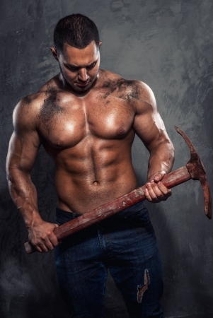 Muscular man holding pickaxe photo