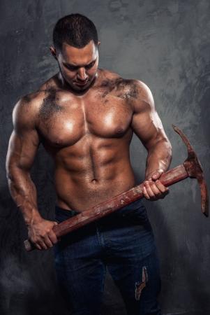 axes: Muscular man holding pickaxe Stock Photo