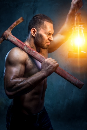 Muscular man holding pickaxe and oil lamp Stock Photo - 20834478