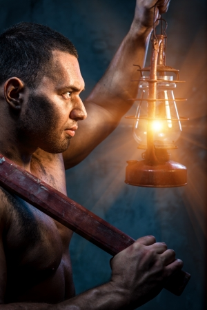 Muscular man holding pickaxe and oil lamp Stock Photo - 20834474