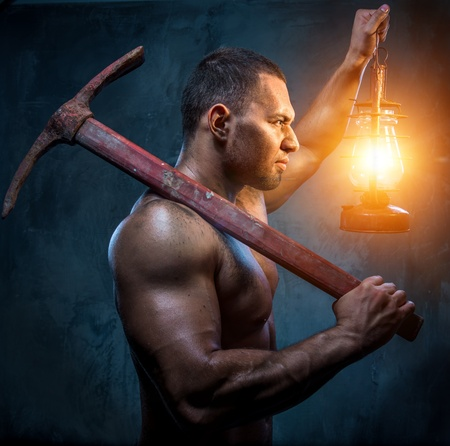 kerosene lamp: Muscular man holding pickaxe and oil lamp