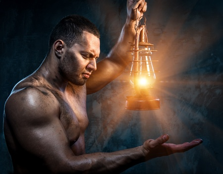 kerosene lamp: Muscular man holding oil lamp