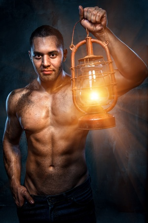 kerosene lamp: Muscular build man holding oil lamp