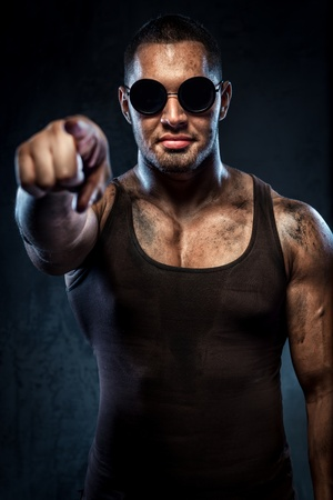 Muscular handsome young man in sunglasses pointing on you photo