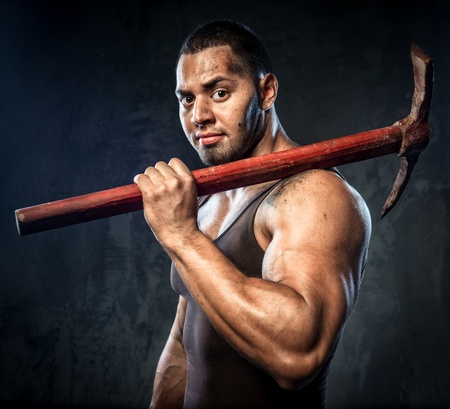 Muscular man holding pickaxe Stock Photo - 20834543