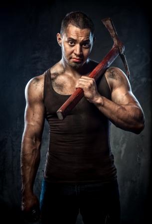 pickaxe: Muscular man holding pickaxe Stock Photo