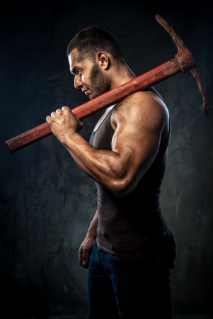 Muscular man holding pickaxe Stock Photo - 20834545