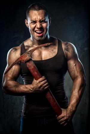 Muscular man holding pickaxe Stock Photo - 20825096