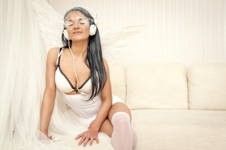 Lovely angel girl in headphones listening music photo