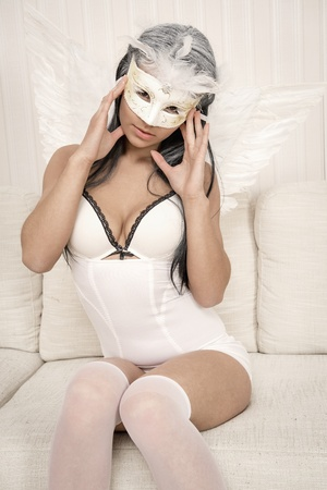 Woman wearing angel wings and carnival mask posing indoors photo