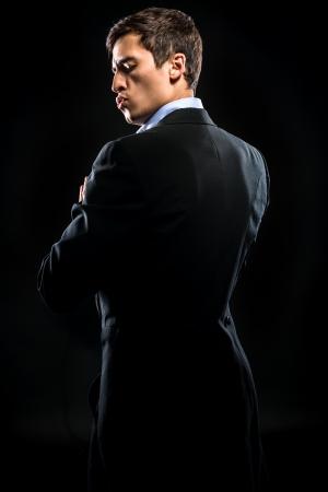 黒の背景にポーズをとってエレガントな黒のスーツを着た男