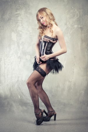 Sexy blond pin up girl posing over grey obsolete background photo