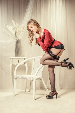 Sexy blond woman wearing black stockings posing indoors photo