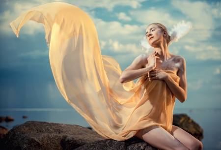 Young beautiful woman as swan posing on the beach at sunset Stock Photo