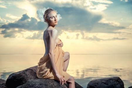 Jonge mooie vrouw als zwaan die op het strand bij zonsondergang Stockfoto