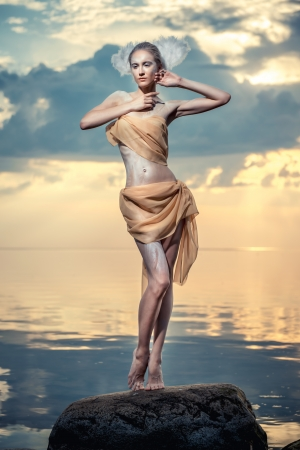 Young beautiful woman as swan posing on the beach at sunset photo