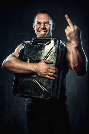 Man with metal fuel can showing middle finger  photo