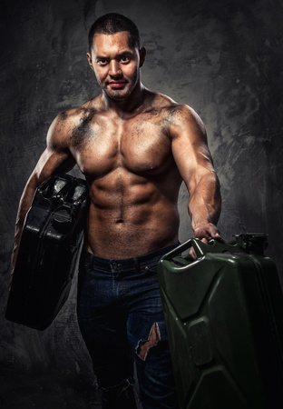 Muscular man with two metal fuel cans indoors photo