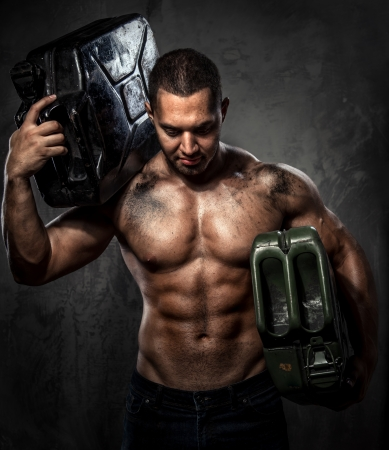 Muscular man with two metal fuel cans indoors Stock Photo