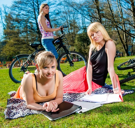 young schoolgirl: Three attractive female students relaxing outdoors