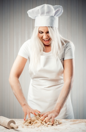 Angry and stressed out woman cook kneading dough  photo