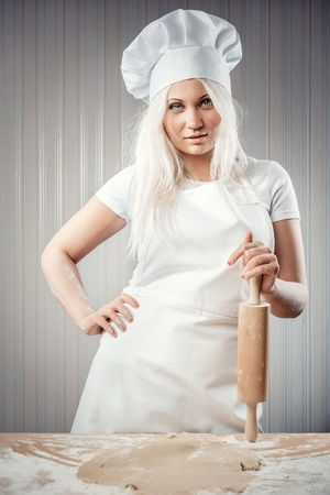 Woman holding rolling pin wearing uniform posing indoors photo