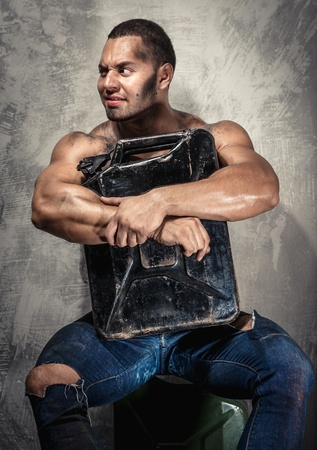 Muscular man with metal fuel can indoors photo
