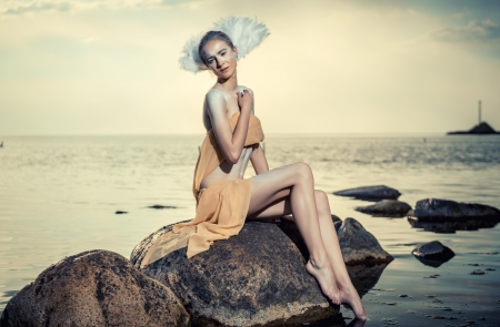 Young beautiful woman as swan posing on the beach  photo