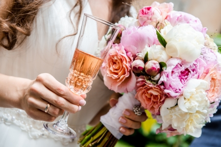 mixed marriage: Beautiful bridal bouquet  and glass of champagne close-up  Stock Photo