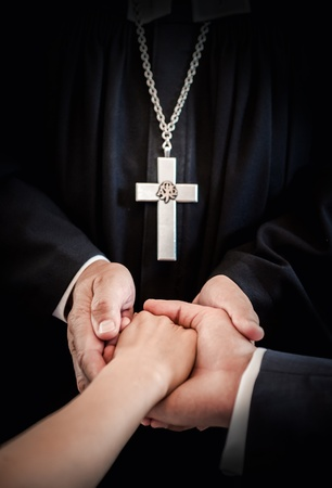 cassock: Priest holding brides and grooms hands during wedding ceremony
